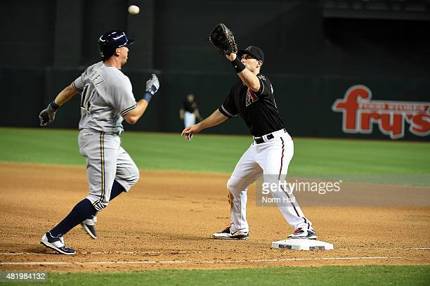 Paul Goldschmidt of the Arizona Diamondbacks covers first base while waiting for the ball as Hernan Perez of the Milwaukee Brewers runs up the line...