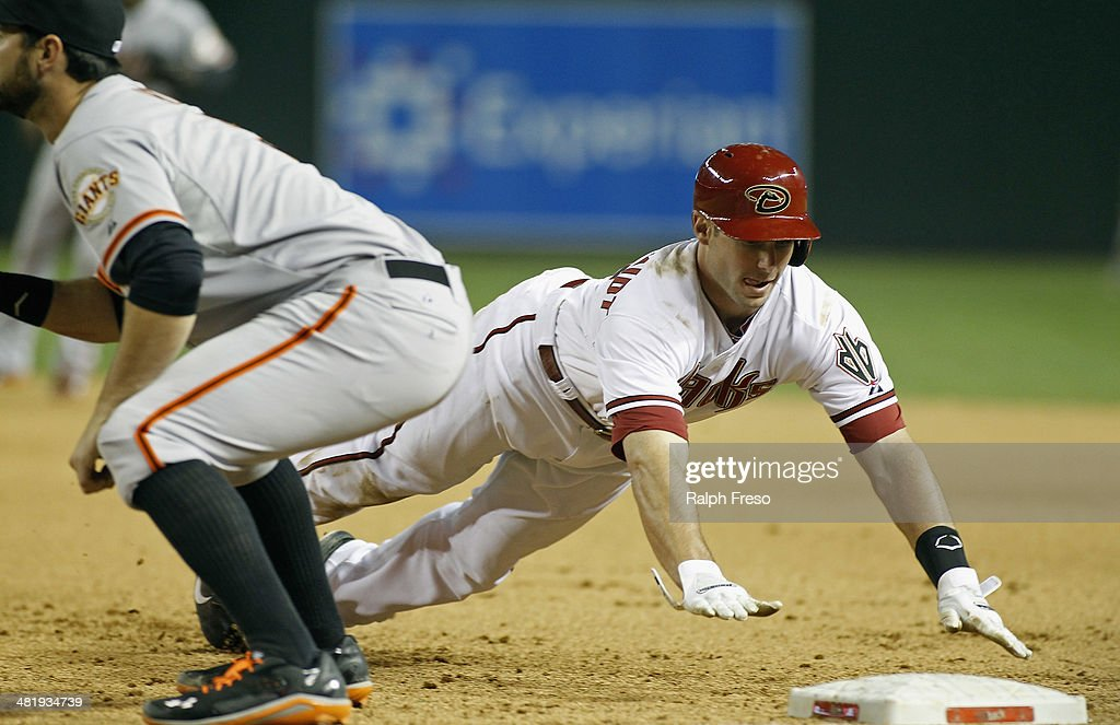 <a gi-track='captionPersonalityLinkClicked' href=/galleries/search?phrase=Paul+Goldschmidt&family=editorial&specificpeople=7511120 ng-click='$event.stopPropagation()'>Paul Goldschmidt</a> #44 of the Arizona Diamondbacks dives back to first base safely as Brandon Belt #9 of the San Francisco Giants waits on the throw during the seventh inning of a MLB game at Chase Field on April 1, 2014 in Phoenix, Arizona.