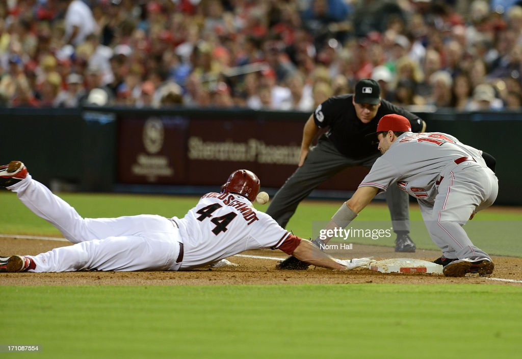 <a gi-track='captionPersonalityLinkClicked' href=/galleries/search?phrase=Paul+Goldschmidt&family=editorial&specificpeople=7511120 ng-click='$event.stopPropagation()'>Paul Goldschmidt</a> #44 of the Arizona Diamondbacks is hit with the ball while diving back to first base as <a gi-track='captionPersonalityLinkClicked' href=/galleries/search?phrase=Joey+Votto&family=editorial&specificpeople=759319 ng-click='$event.stopPropagation()'>Joey Votto</a> #19 of the Cincinnati Reds tries to come up with the throw at Chase Field on June 21, 2013 in Phoenix, Arizona.