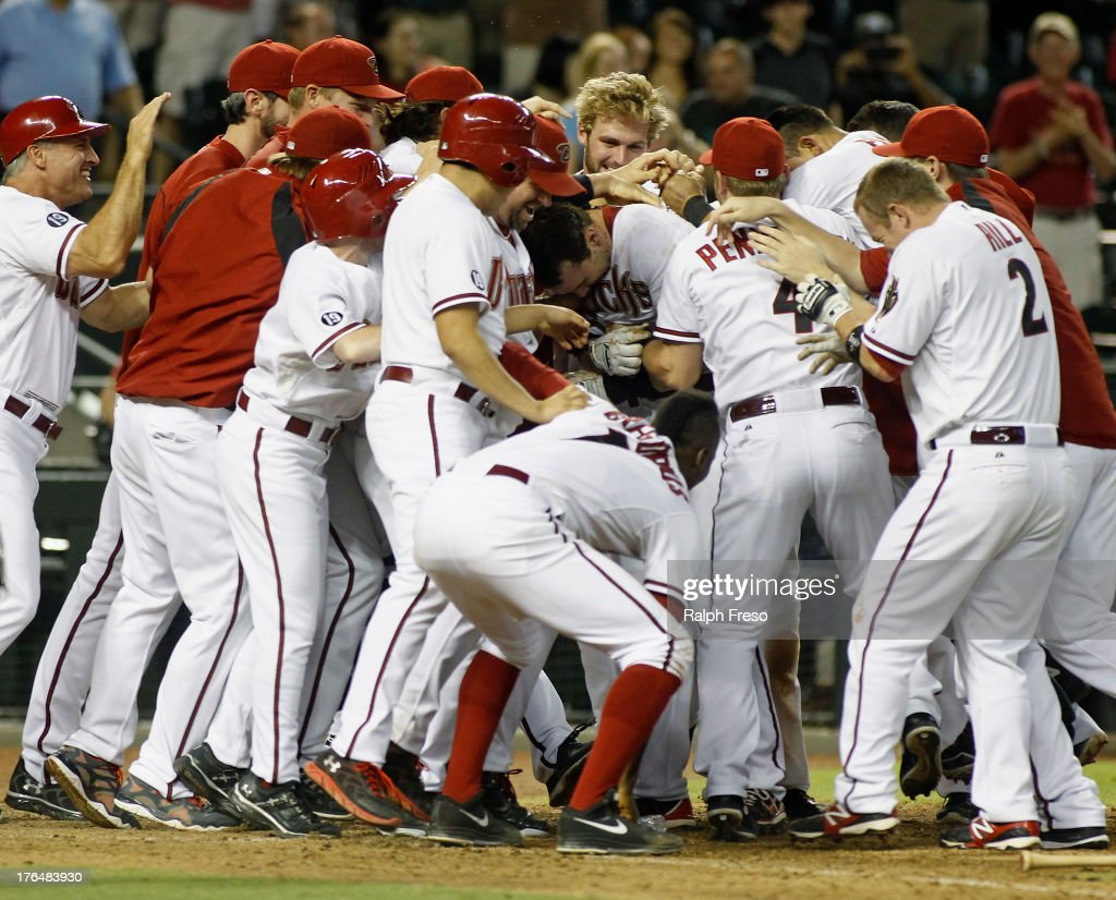 <a gi-track='captionPersonalityLinkClicked' href=/galleries/search?phrase=Paul+Goldschmidt&family=editorial&specificpeople=7511120 ng-click='$event.stopPropagation()'>Paul Goldschmidt</a> #44 of the Arizona Diamondbacks (center) is swarmed by teammates as he crosses home plate following his game-winning walk off home run against the Baltimore Orioles in the eleventh inning of a MLB game at Chase Field on August 13, 2013 in Phoenix, Arizona. The Diamondbacks defeated the Orioles 4-3.