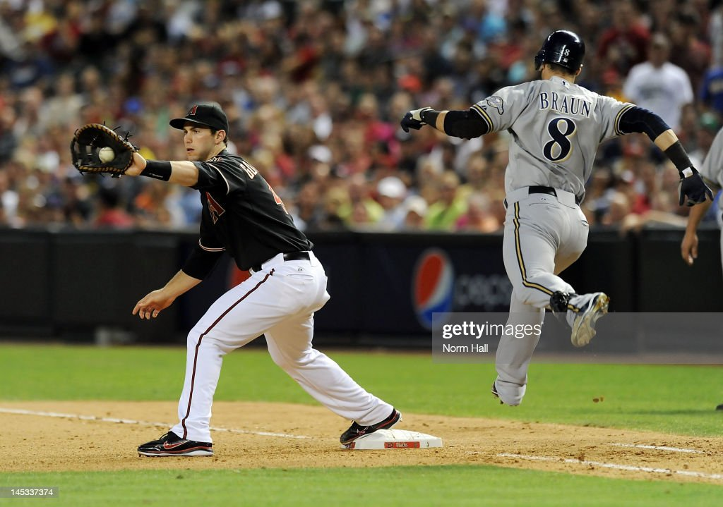 Paul Goldschmidt of the Arizona Diamondbacks makes a catch at first base as Ryan Braun of the Milwaukee Brewers attempts to beat out the throw at...