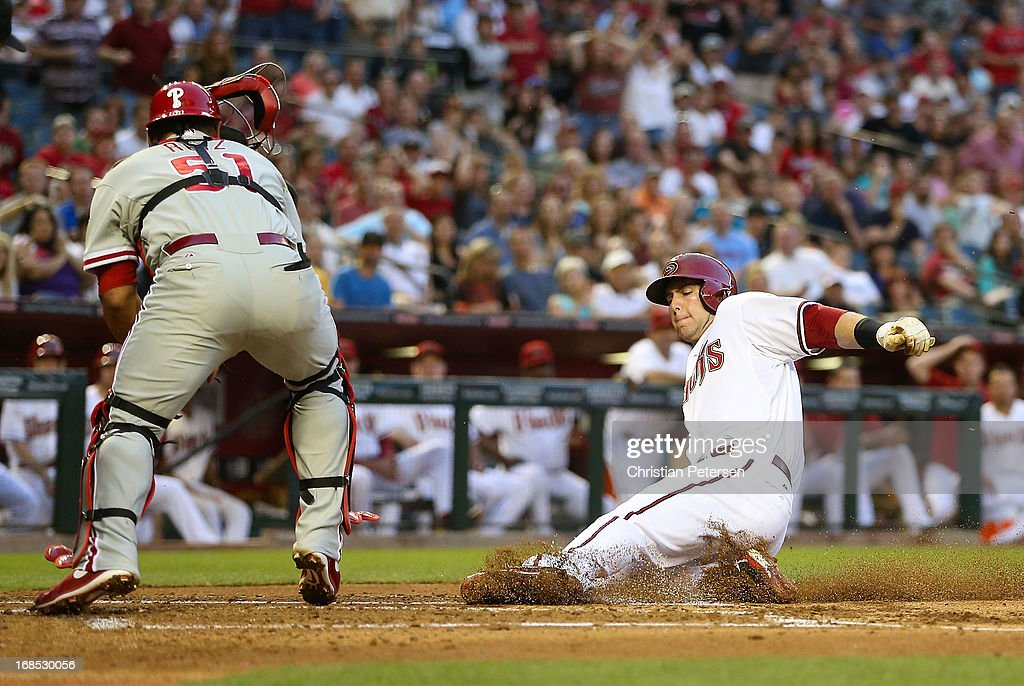 Paul Goldschmidt of the Arizona Diamondbacks safely slides into home plate to score a run ahead of the tag from catcher Carlos Ruiz of the...