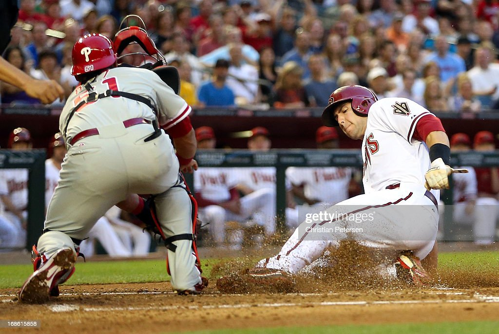 <a gi-track='captionPersonalityLinkClicked' href=/galleries/search?phrase=Paul+Goldschmidt&family=editorial&specificpeople=7511120 ng-click='$event.stopPropagation()'>Paul Goldschmidt</a> #44 of the Arizona Diamondbacks safely slides into home plate to score a run ahead of the tag from catcher Carlos Ruiz #51 of the Philadelphia Phillies during the first inning of the MLB game at Chase Field on May 10, 2013 in Phoenix, Arizona. The Diamondbacks defeated the Phillies 3-2.