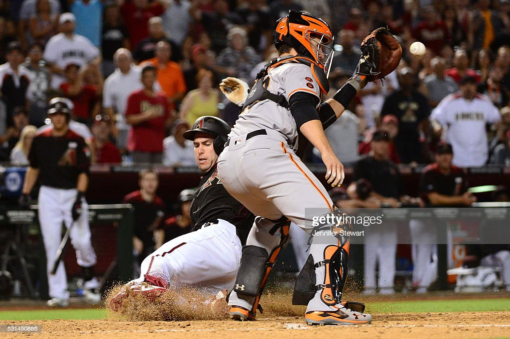 Paul Goldschmidt of the Arizona Diamondbacks safely slides into home in front of Buster Posey of the San Francisco Giants in the eighth inning at...