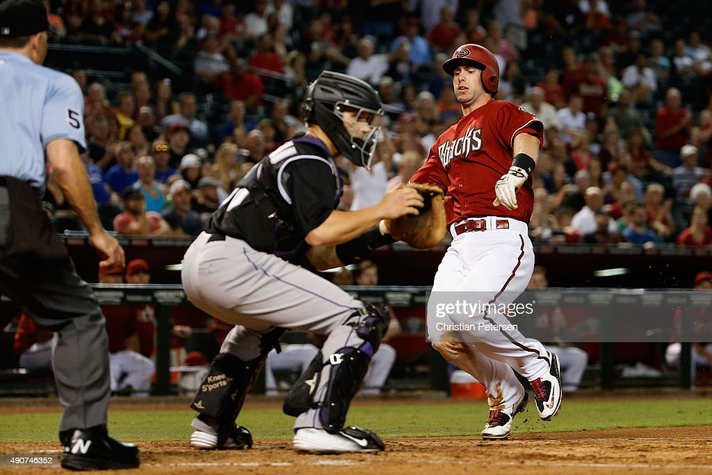 Paul Goldschmidt #44 of the Arizona Diamondbacks slides into home plate to score a sixth inning run past catcher Dustin Garneau #50 of the Colorado Rockies during the MLB game at Chase Field on September 30, 2015 in Phoenix, Arizona.