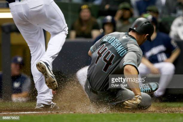 Paul Goldschmidt of the Arizona Diamondbacks slides into home plate to score a run on a wild pitch past Jared Hughes of the Milwaukee Brewers in the...