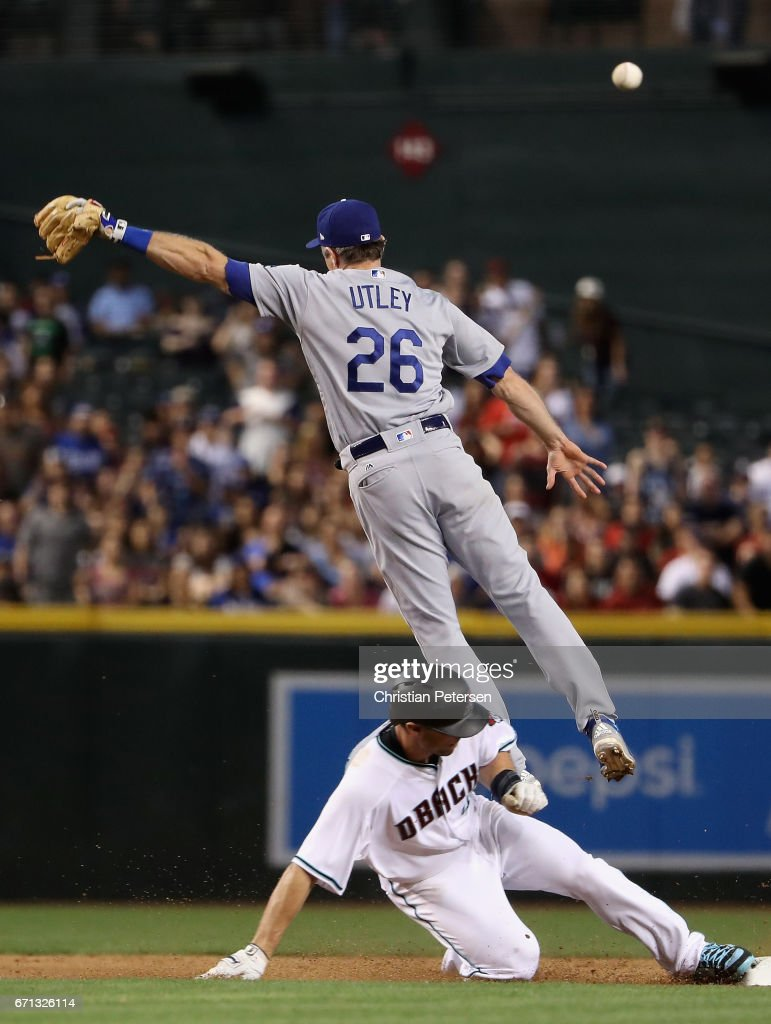 Paul Goldschmidt #44 of the Arizona Diamondbacks slides into second base as infielder Chase Utley #26 of the Los Angeles Dodgers attempts to catch the throw during the seventh inning of the MLB game at Chase Field on April 21, 2017 in Phoenix, Arizona.
