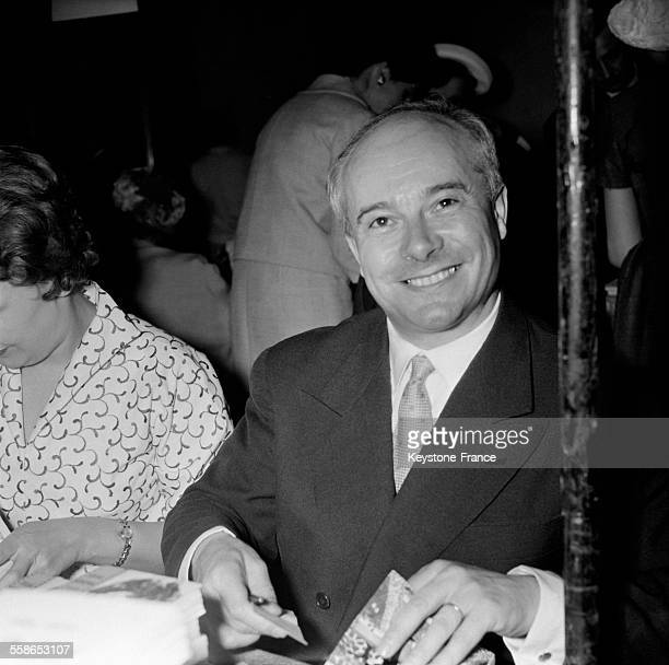 Paul Guth photographié à la vente annuelle des écrivains combattants à la Maison de la Chimie à Paris France le 2 mai 1958
