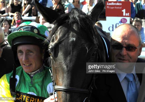 Paul Hanagan stands with Wooton Bassett and trainer Richard Fahey after their victory in the Weatherbys Insurance 300000 2 Y O Stakes on The DFS...