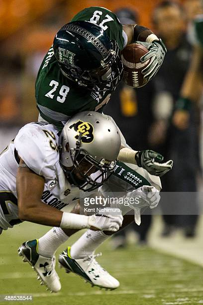 Paul Harris of the Hawaii Warriors is stopped by Ahkello Witherspoon of the Colorado Buffaloes during the second half of a college football game at...