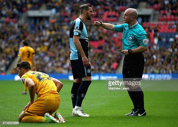 Paul Hayes of Wycombe Wanderers receives a yellow card from referee Simon Hooper after his challenge on Stephen McLaughlin of Southend United during...