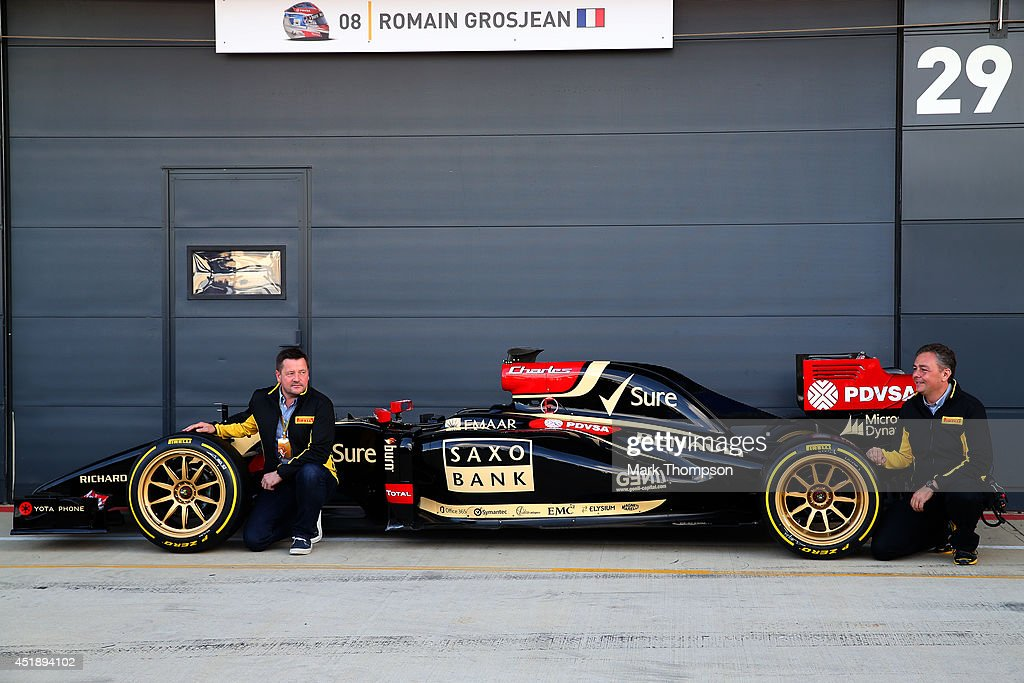 Paul Hembery (L), Motorsport Director of Pirelli poses with the new 18-inch Pirelli wheels, fitted on a Lotus, before demonstration runs during day two of testing at Silverstone Circuit on July 9, 2014 in Northampton, England.