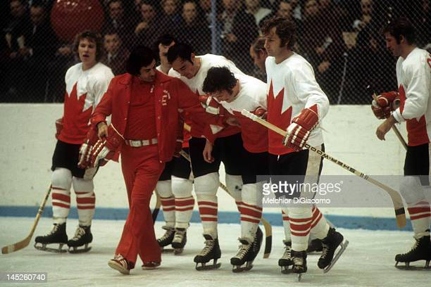 Paul Henderson of Canada is helped back to the bench by trainer Joe Sgro teammates Frank Mahovlich and Rod Seiling during Game 5 of the 1972 Summit...