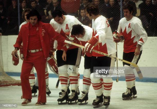 Paul Henderson of Canada is helped back to the bench by trainer Joe Sgro teammates Frank Mahovlich Rod Seiling and Jean Ratelle during Game 5 of the...