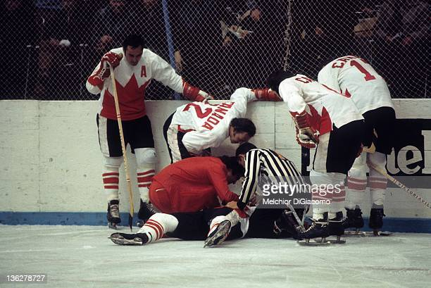 Paul Henderson of Canada lays on the ground after crashing into the boards as trainer Joe Sgro checks him out while teammates Frank Mahovlich Yvan...