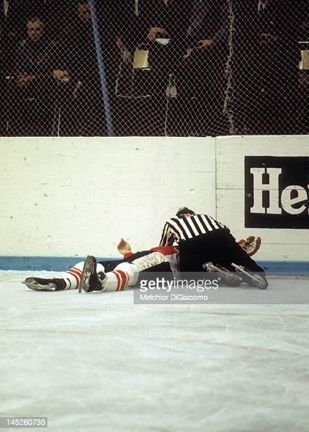 Paul Henderson of Canada lays on the ground after crashing into the boards as the referee checks him out during Game 5 of the 1972 Summit Series on...