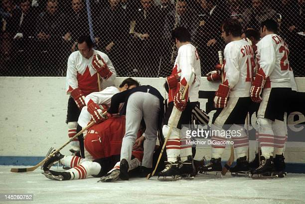 Paul Henderson of Canada lays on the ground after crashing into the boards as trainer Joe Sgro checks him out while teammates Frank Mahovlich Jean...