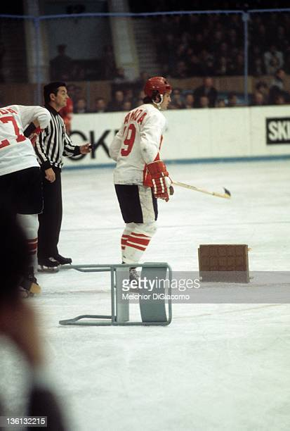 Paul Henderson of Canada skates by a chair thrown onto the ice by Canadian coach Harry Sinden after the referees made some questionable calls during...