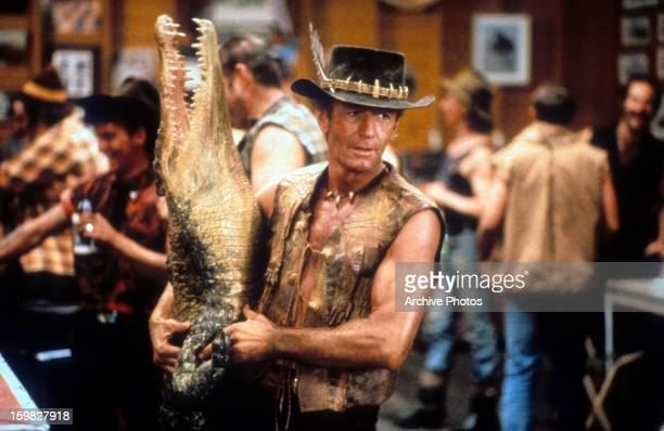 Paul Hogan carrying dead crocodile in bar in a scene from the film 'Crocodile Dundee' 1986