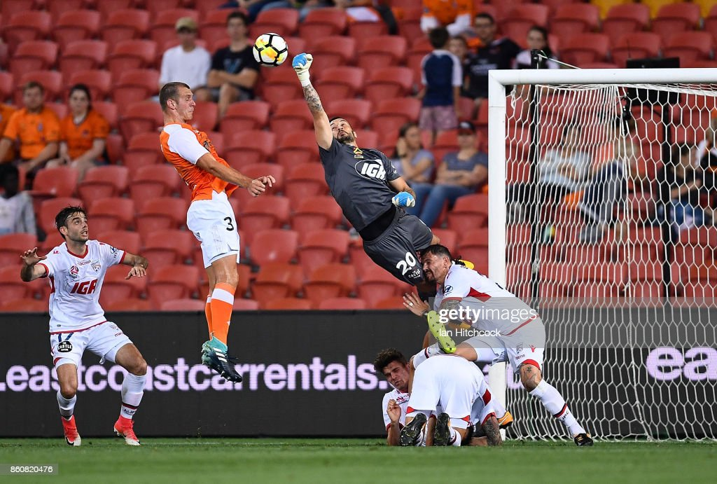 Paul Izzo of Adelaide United punches the ball away ahead of Luke De Vere of the Roar during the round two A-League match between the Brisbane Roar and Adelaide United at Suncorp Stadium on October 13, 2017 in Brisbane, Australia.