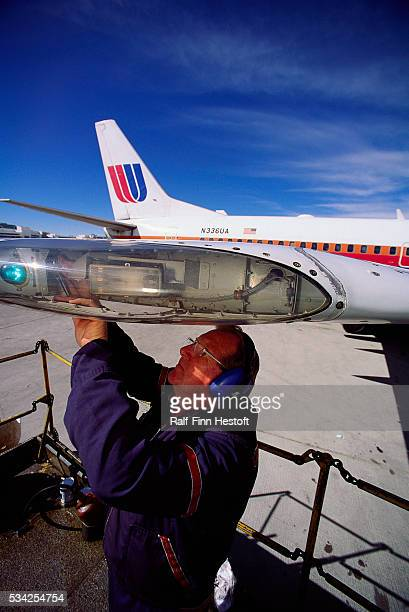 Paul Johnson changes a light bulb on the wing of a Boeing 737300 airplane at Denver International Airport | Location Near Denver Colorado USA