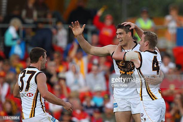 Paul Johnson of the Hawks celebrates kicking a goal with teamates Brendan Whitecross and Rick Ladson during the round 24 AFL match between the Gold...