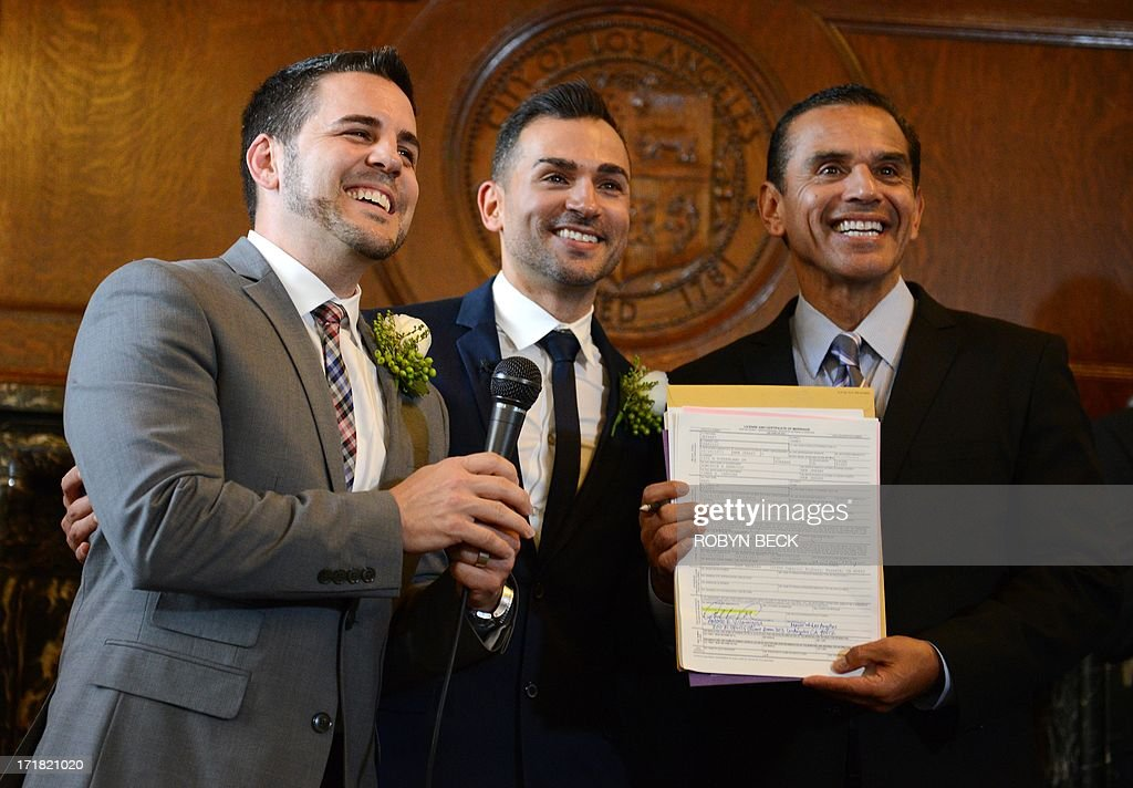 Paul Katami (L), his husband Jeff Zarrillo (C) and Los Angeles Mayor Antonio Villaraigosa hold up the marriage license after Villaraigosa married them at Los Angeles City Hall June 28, 2013. Katami and Zarrillo and the other two plaintiffs in the U.S. Supreme Court case that overturned California's same-sex marriage ban were married June 28, after a federal appeals court freed gay couples to obtain marriage licenses in the state for the first time in 4 1/2 years. AFP PHOTO / ROBYN BECK