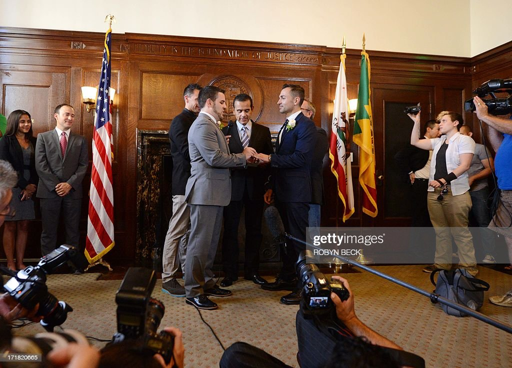 Paul Katami (L) places the wedding ring on the finger of his partner Jeff Zarrillo (R) as they are officially married by Los Angeles Mayor Antonio Villaraigosa (C) at Los Angeles City Hall June 28, 2013, becoming one of the first gay couples to marry in California since the Supreme Court refused to rule on Proposition 8 on June 26.
