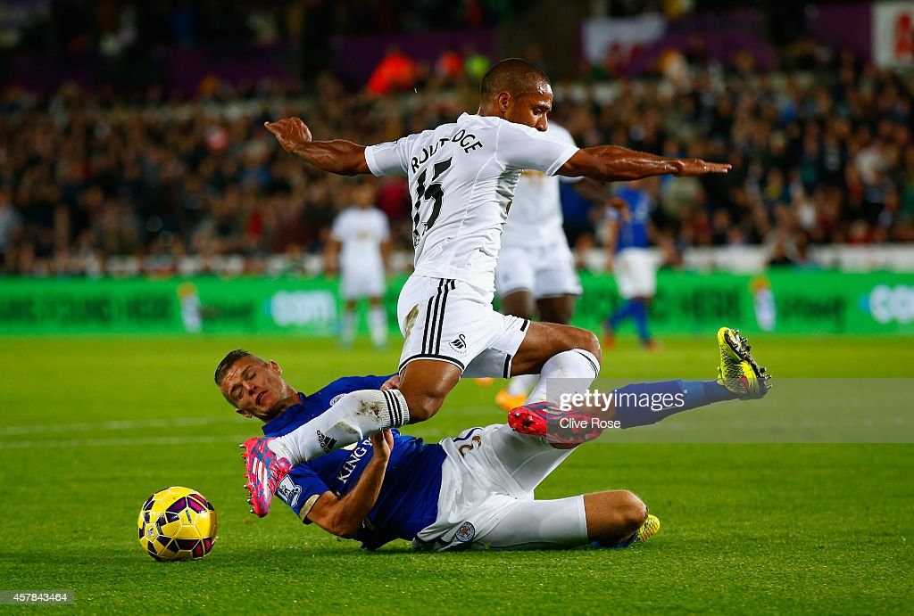 Paul Konchesky of Leicester City tackles Wayne Routledge of Swansea City during the Barclays Premier League match between Swansea City and Leicester City at Liberty Stadium on October 25, 2014 in Swansea, Wales.