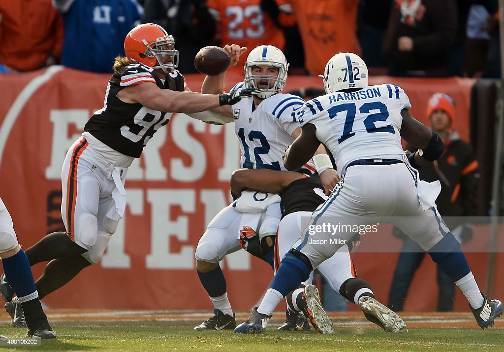 Paul Kruger #99 of the Cleveland Browns hits Andrew Luck #12 of the Indianapolis Colts and forces a fumble which is recovered for a touchdown during the first quarter at FirstEnergy Stadium on December 7, 2014 in Cleveland, Ohio.