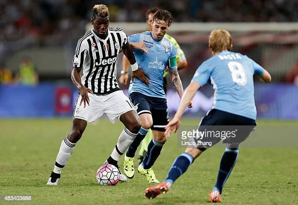 Paul Labile Pogba of Juventus FC challenges Lucas Biglia and Dusan Basta of Lazio during the Italian Super Cup final football match between Juventus...