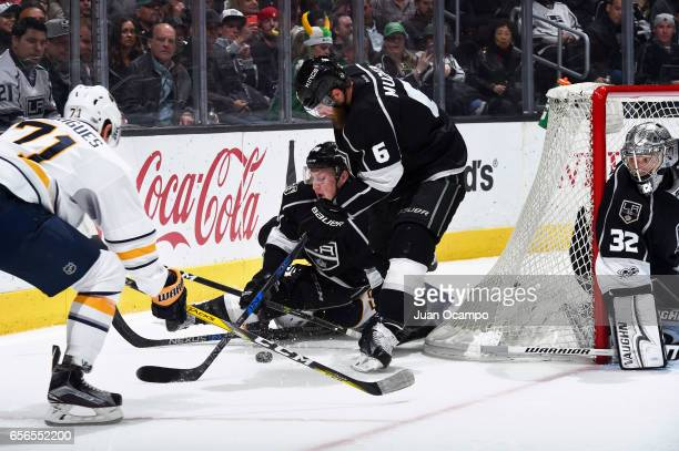 Paul LaDue and Jake Muzzin of the Los Angeles Kings battle for the puck against Evan Rodrigues of the Buffalo Sabres as Jonathan Quick of the Los...