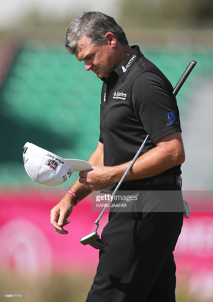 Paul Lawrie of Scotland holds his cap and club during the first round of the Qatar Masters Golf tournament in Doha on January 23, 2013.
