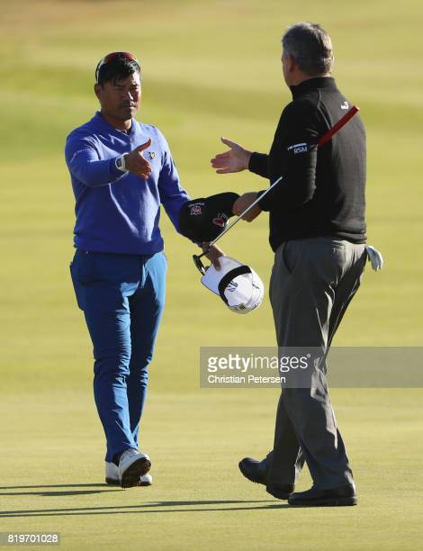 Paul Lawrie of Scotland shakes hands with Yusaku Miyazato of Japan on the 18th hole during the first round of the 146th Open Championship at Royal...