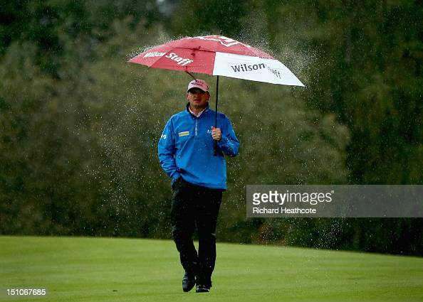Paul Lawrie of Scotland shakes the rain from his umbrella as he walks up the 15th fairway during the second round of the Omega European Masters at...
