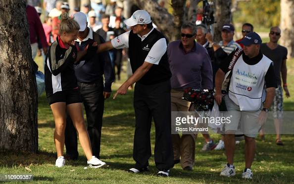 Paul Lawrie of Scotland stops a young spectator from stepping on hs ball on the 18th hole during the third round of the Open de Andalucia at the...