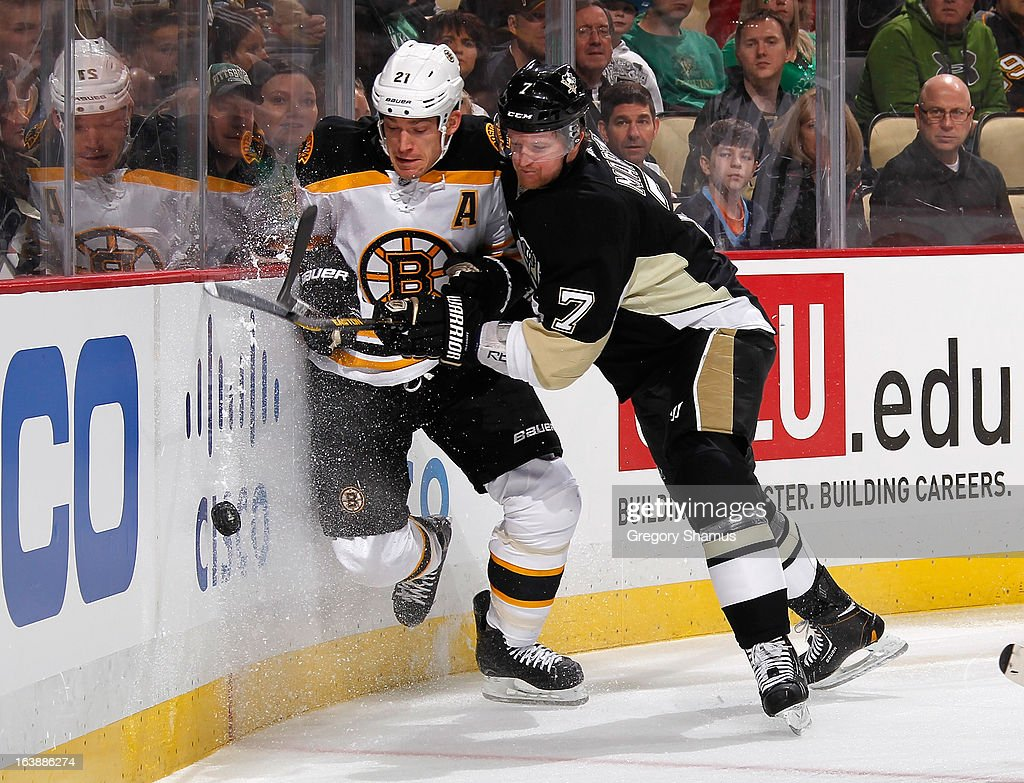 Paul Martin #7 of the Pittsburgh Penguins battles for the loose puck against <a gi-track='captionPersonalityLinkClicked' href=/galleries/search?phrase=Andrew+Ference&family=editorial&specificpeople=202264 ng-click='$event.stopPropagation()'>Andrew Ference</a> #21 of the Boston Bruins on March 17, 2013 at Consol Energy Center in Pittsburgh, Pennsylvania.