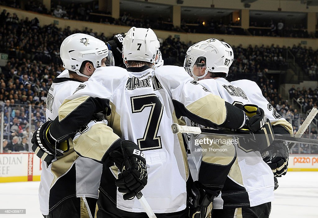 Paul Martin #7 of the Pittsburgh Penguins celebrates his third period goal against the Winnipeg Jets with teammates at the MTS Centre on April 3, 2014 in Winnipeg, Manitoba, Canada.