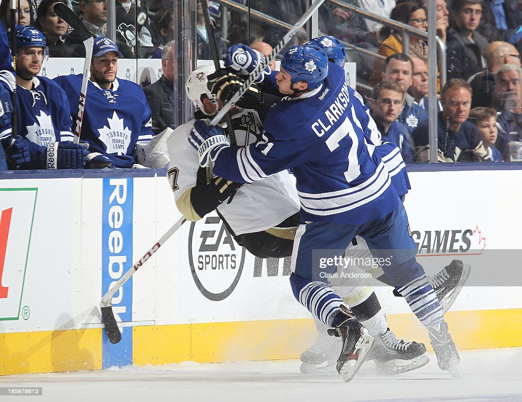 Paul Martin #7 of the Pittsburgh Penguins is hammered by David Clarkson #71 of the Toronto Maple Leafs during an NHL game at the Air Canada Centre on October 26, 2013 in Toronto, Ontario, Canada. The Leafs defeated the Penguins 4-1.