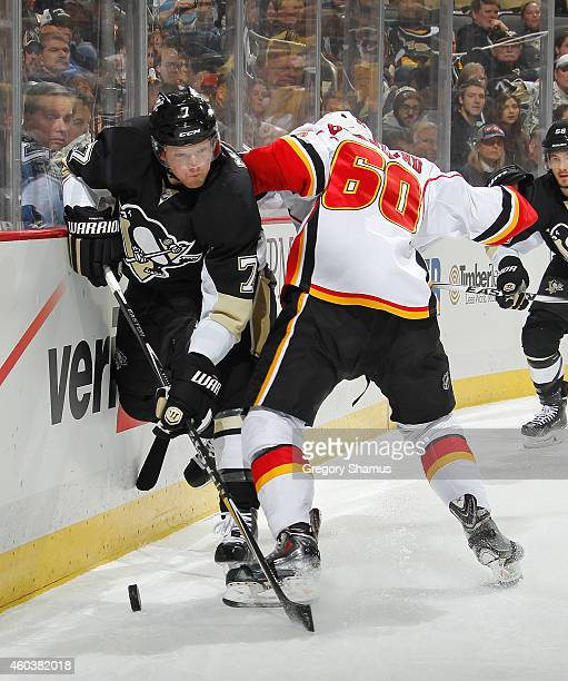 Paul Martin of the Pittsburgh Penguins tries to get past the defense of Markus Granlund of the Calgary Flames at Consol Energy Center on December 12...