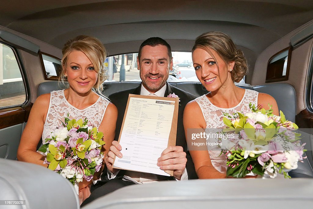 Paul McCarthy, along with flower girl Amanda Wenham (L) and matron of honour Tracey Moloney, poses with his marriage certificate prior to his wedding ceremony at the Museum of New Zealand, Te Papa, on August 19, 2013 in Wellington, New Zealand. Australian gay couple Paul McCarthy and Trent Kandler were flown to Wellington by Tourism New Zealand in a promotion to highlight to Australians that same-sex marriage is legal in New Zealand.