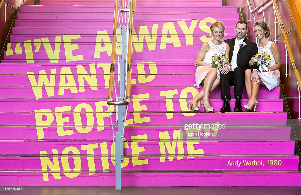 Paul McCarthy, along with flower girl Amanda Wenham (L) and matron of honour Tracey Moloney, pose with an Andy Warhol quote at the Museum of New Zealand, Te Papa, on August 19, 2013 in Wellington, New Zealand. Australian gay couple Paul McCarthy and Trent Kandler were flown to Wellington by Tourism New Zealand in a promotion to highlight to Australians that same-sex marriage is legal in New Zealand.