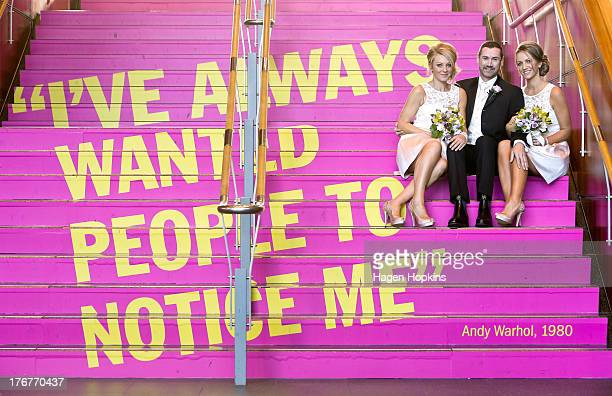 Paul McCarthy along with flower girl Amanda Wenham and matron of honour Tracey Moloney pose with an Andy Warhol quote at the Museum of New Zealand Te...