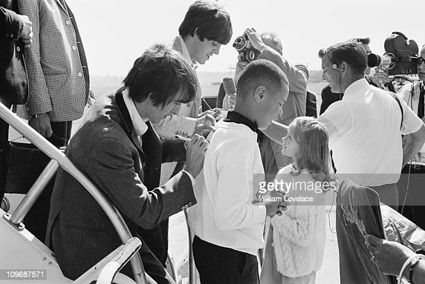 Paul McCartney and George Harrison of The Beatles sign autographs for fans during their US tour August 1964