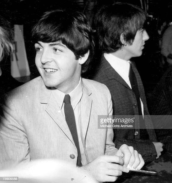 Paul McCartney and George Harrison of the rock and roll band 'The Beatles' pose for a portrait during a press conference backstage at their concert...