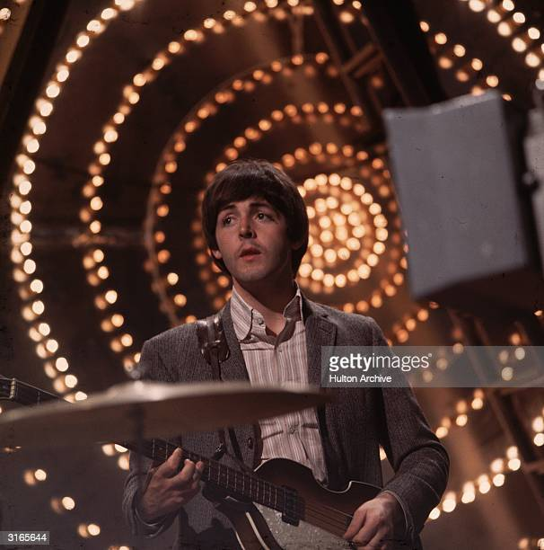 Paul McCartney bassist and songwriter with The Beatles performing against a lit backdrop