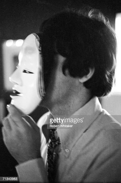 Paul McCartney behind a decorative mask in the Beatles' suite at the Tokyo Hilton hotel June/July 1966