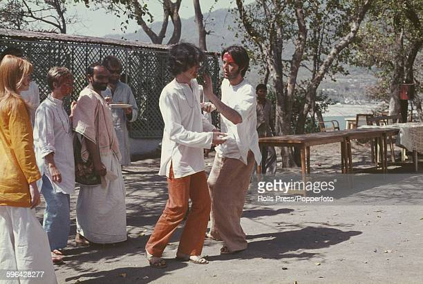 Paul McCartney from The Beatles pictured daubing red paint on the face of Scottish singer Donovan watched by Jane Asher on left and fellow guests...