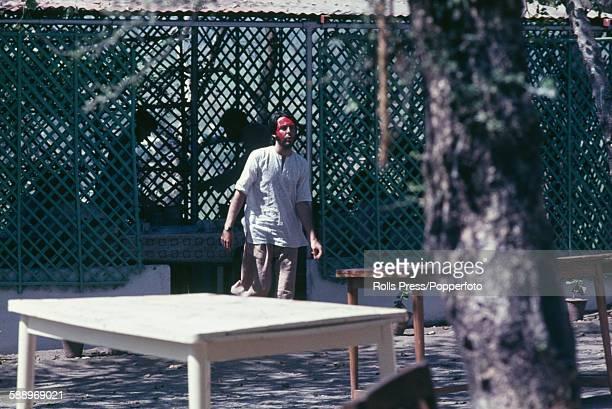 Paul McCartney from The Beatles pictured wearing red face paint as he walks through the Chaurasi Kutia ashram compound of Maharishi Mahesh Yogi near...