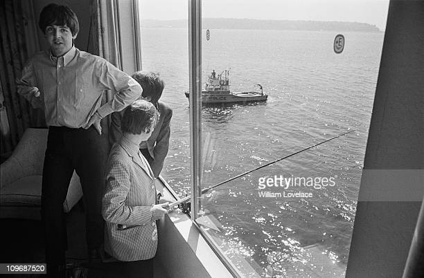 Paul McCartney George Harrison and Ringo Starr of The Beatles fishing from their hotel room at the Edgewater Inn Seattle Washington 24th August 1964...